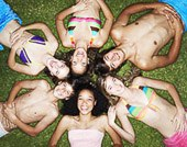 Overhead view of six teenagers in swimsuits laying on grass with heads together