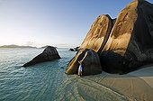 Woman relaxing on granite boulders Anse Source d'Argent