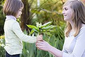 Lily of the Valley Girl feeling held by a teenage France ; The child is 4 years old, the teenager 16