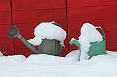 Watering cans in the snow in a garden
