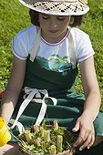 Little girl making an insect shelter in a garden